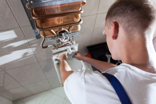 Heating engineer servicing a boiler; boiler service cost