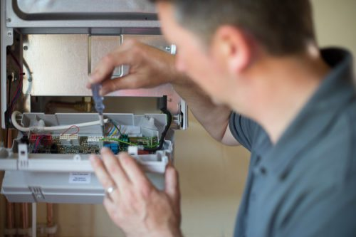 Heating professional checking on a boiler